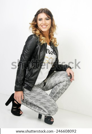 portrait of a Young smiling caucasian teenager seating on a White background wearing grey jeans White shirt and a black leather jacket - stock photo