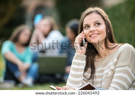 Portrait of a young, smiling college girl with blurred students are sitting in the park. She is speaking by phone. - stock photo