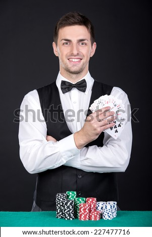 Portrait of a young smiling croupier with gambling chips on the green table and playing cards. - stock photo