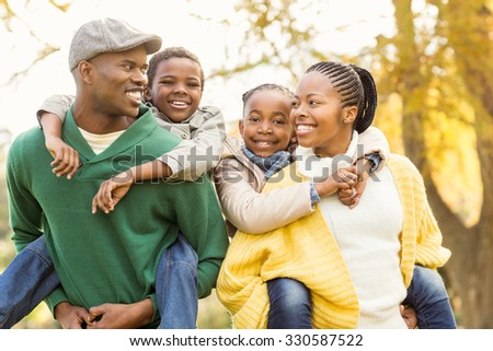 Portrait of a young smiling family in piggyback on an autumns day