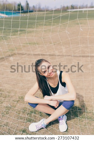 Portrait of a young smiling girl goes in for sports in the summer. Resting outdoors.