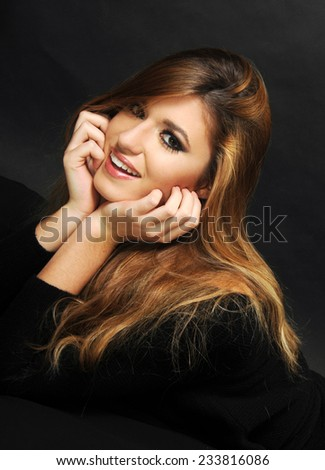 portrait of a young smiling longhaired blond girl with perfect skin and teeth framing her face with her hands - stock photo