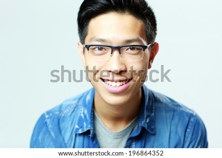 Portrait of a young smiling man in glasses on gray background - stock photo