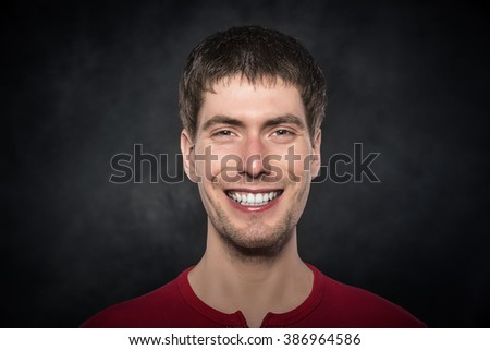 Portrait of a young smiling man over dark background. - stock photo