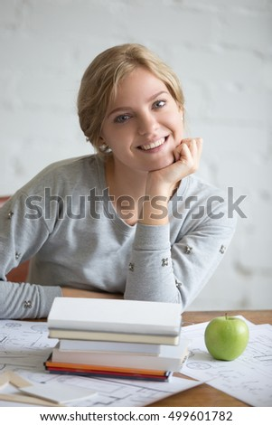 Portrait of a young smiling student girl sitting at the desk with books and green apple, propping up chin in her hand. Education concept photo, looking at the camera, vertical