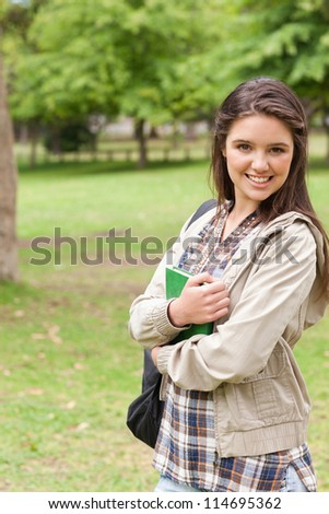 Portrait of a young smiling student holding textbook while posing in a park - stock photo