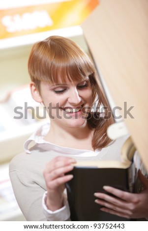 portrait of a young  smiling student in a library - stock photo