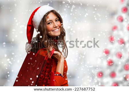 Portrait of a young smiling woman doing shopping before christmas - stock photo