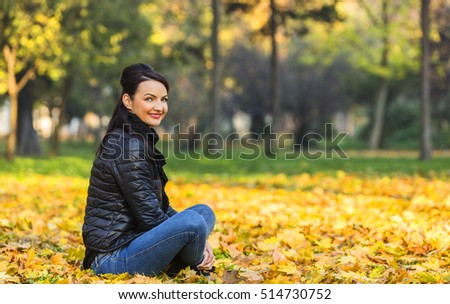 Portrait of a young smiling woman in a yellow autumn forest.