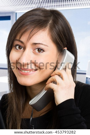 Portrait of a young smiling woman talking on the phone
