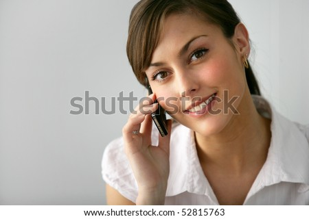 Portrait of a young smiling woman with a phone - stock photo