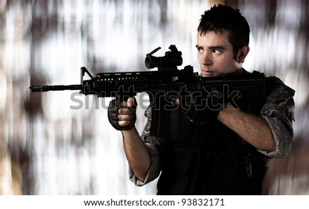 portrait of a young soldier aiming with a rifle against a blurred light background