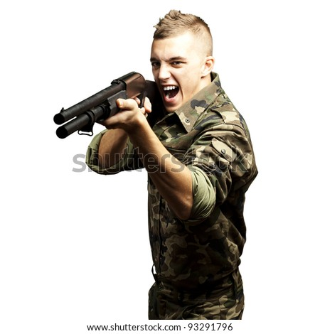 portrait of a young soldier aiming with a shotgun against a white background - stock photo