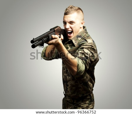 portrait of a young soldier aiming with shotgun over grey background - stock photo