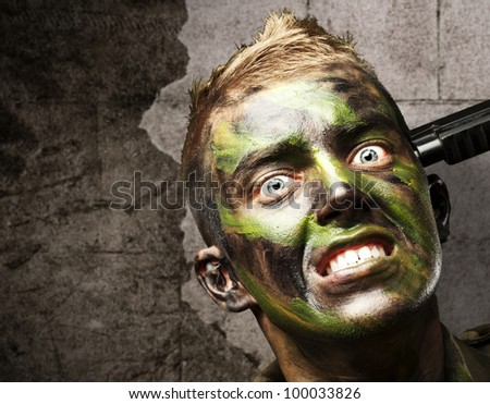 portrait of a young soldier comiting suicide against a grunge wall