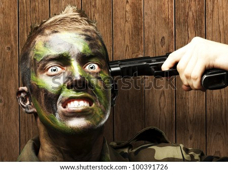 portrait of a young soldier comiting suicide against a wooden wall - stock photo