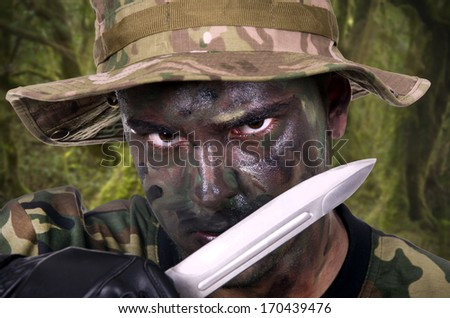 portrait of a young soldier painted with jungle camouflage very serious  - stock photo