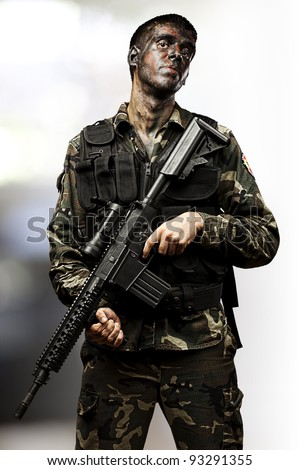 portrait of a young soldier posing and holding a modern rifle against an abstract background