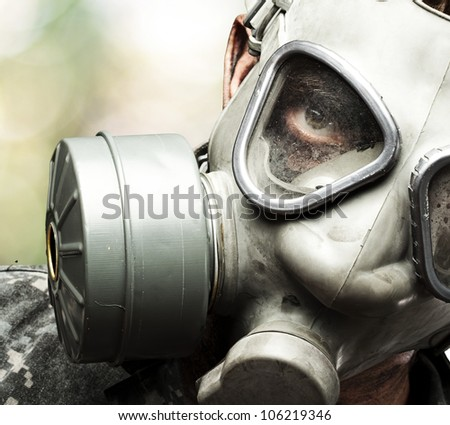 portrait of a young soldier wearing a gas mask against a nature background