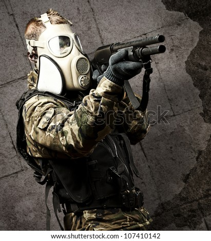 portrait of a young soldier with a gas mask aiming with a shotgun against a grunge wall - stock photo