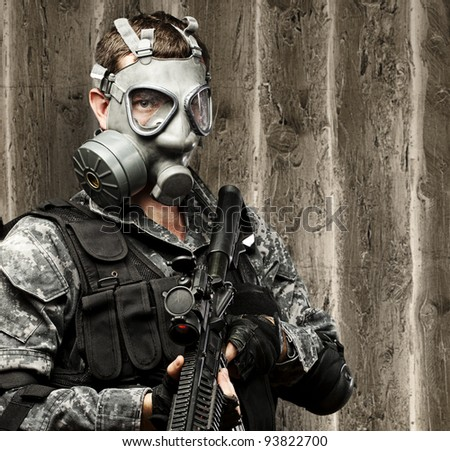 portrait of a young soldier with a gas mask and a rifle against a grunge wooden background