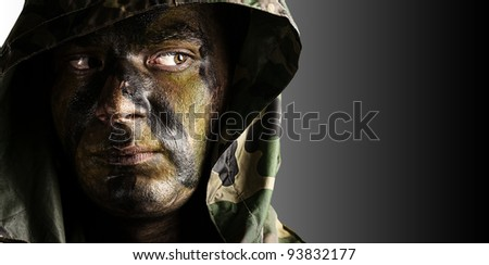 portrait of a young soldiers face with a hood against a black and white background