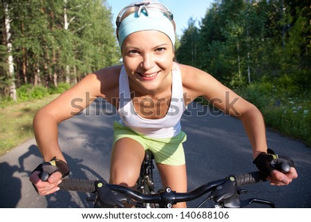 Portrait of a young sports cute girl on a bicycle in the park - stock photo