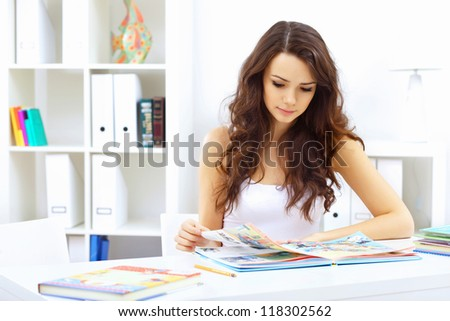 Portrait of a young student girl sitting at the table - stock photo