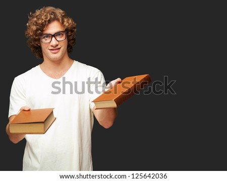 Portrait Of A Young Student Holding Books On Black Background