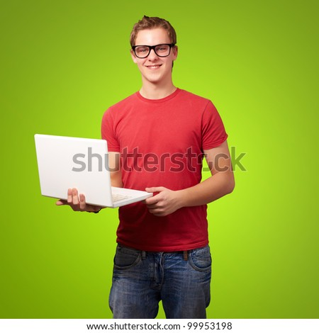 portrait of a young student man holding a laptop over a green background
