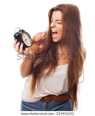 portrait of a young student screaming to alarm clock - stock photo