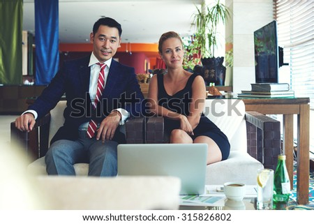 Portrait of a young successful business men and woman working together on common projects, smiling male and female posing for the camera while sitting in front open laptop computer in office space - stock photo