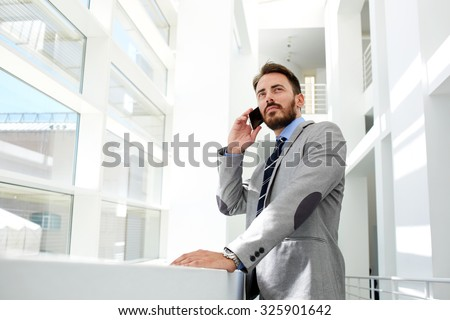 Portrait of a young successful businessman speaking on the mobile phone while standing in the modern office interior, handsome confident male entrepreneur talking on the cell telephone during break  - stock photo