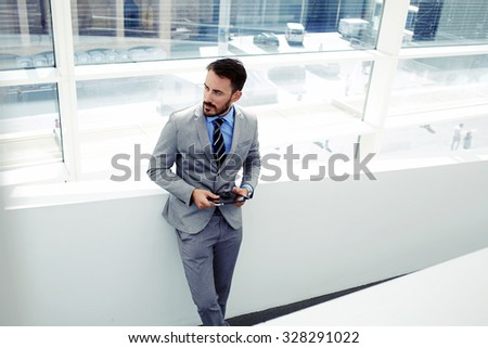 Portrait of a young successful man economist holding his touch pad while standing in modern office interior, confident male dressed in luxury corporate clothes using digital tablet during work break   - stock photo