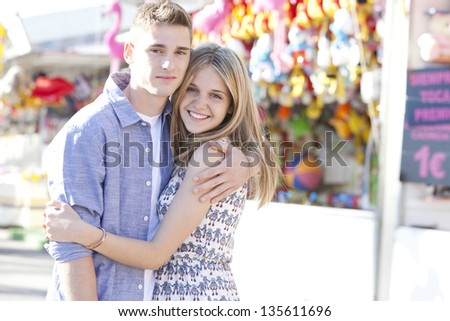 Portrait of a young teenage couple hugging while enjoying together being in a funfair ground with games and toy prices, smiling. - stock photo