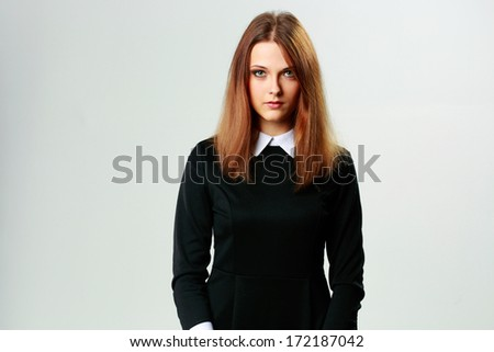 Portrait of a young thoughtful woman in formal dress on gray background - stock photo