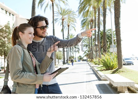 Portrait of a young tourist couple on vacation in a destination city palm trees boulevard, holding a technology tablet during a sunny day and pointing ahead.