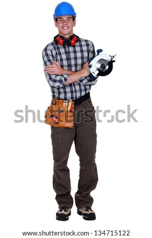 Portrait of a young tradesman holding a circular saw - stock photo