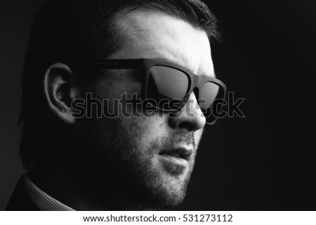 Portrait of a young trendy man in sunglasses in a dark room close up. Black and white photography