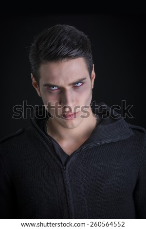 Portrait of a Young Vampire Man with Black Sweater, Looking at the Camera, on a Dark Smoky Background. - stock photo