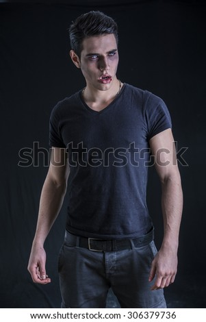 Portrait of a Young Vampire Man with Black T-Shirt, Looking to Right, on a Dark Smoky Background. - stock photo