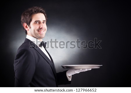 Portrait of a young waiter holding an empty dish on black background - stock photo