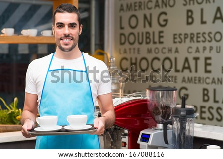 Portrait of a young waiter with cups of coffee in the coffeehouse  - stock photo