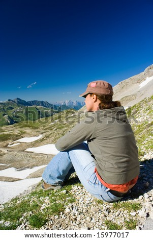 Portrait of a young woman admiring the beautiful view of Alps - stock photo
