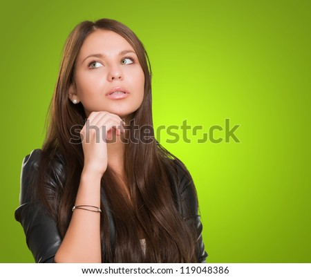 Portrait Of A Young Woman against a green background - stock photo