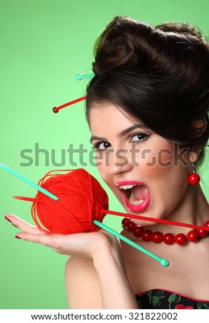 Portrait of a young woman and a ball of yarn with knitting . pin-up girl  - stock photo