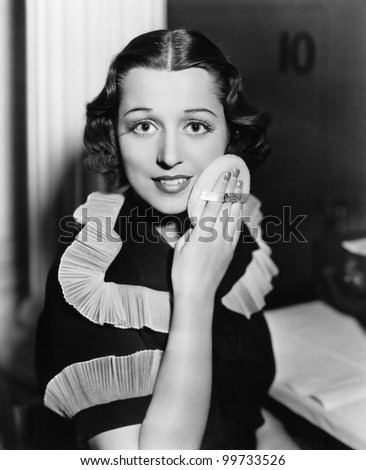 Portrait of a young woman applying powder to her face - stock photo