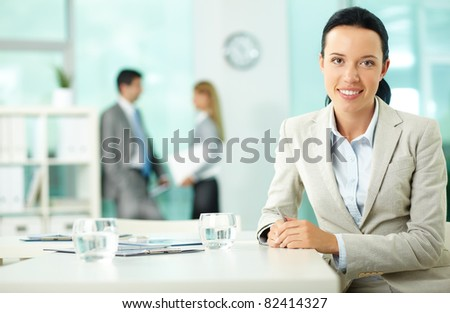 Portrait of a young woman at workplace looking at camera in working environment - stock photo