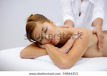 Portrait of a young woman being massaged - stock photo
