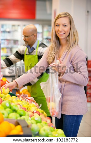 Portrait of a young woman buying fruits with shop assistant in the background - stock photo